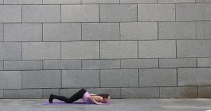 La mujer practica ejercicio de la aptitud de la yoga en la estera rosada en la ciudad en fondo urbano gris metrajes
