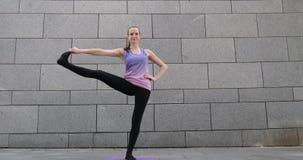 La mujer practica ejercicio de la aptitud de la yoga en la estera rosada en la ciudad en fondo urbano gris almacen de video