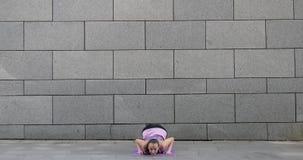 La mujer practica ejercicio de la aptitud de la yoga en la estera rosada en la ciudad en fondo urbano gris almacen de metraje de vídeo