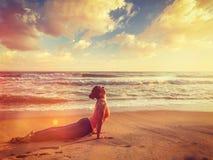 La mujer practica el asana Urdhva Mukha Svanasana de la yoga en la playa Foto de archivo