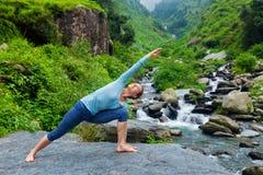 La mujer practica el asana Utthita Parsvakonasana de la yoga al aire libre Imágenes de archivo libres de regalías