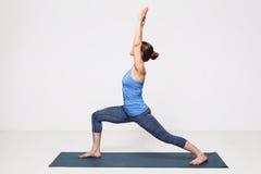 La mujer practica el utthita Virabhadrasana del asana de la yoga Imagen de archivo libre de regalías