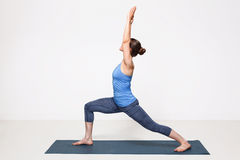 La mujer practica el utthita Virabhadrasana del asana de la yoga Imagenes de archivo