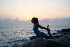 La mujer practica yoga en el amanecer, hay un asana en una piedra, amanecer y una imagen de la muchacha, disfrutar de amanecer, p Fotos de archivo libres de regalías