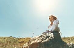 La mujer practica yoga y medita en la posición de loto respecto a mounta Foto de archivo libre de regalías