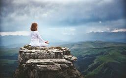La mujer practica yoga y medita en la posición de loto respecto a mounta Foto de archivo