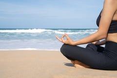 La mujer practica yoga y medita en la posición de loto respecto a la playa imagen de archivo libre de regalías