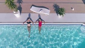 La mujer preciosa de los amigos en el traje de baño está descansando en piscina azul el vacaciones de verano almacen de metraje de vídeo