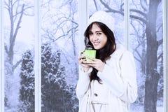 La mujer preciosa en abrigo de invierno bebe el café Imágenes de archivo libres de regalías