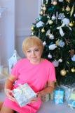 La mujer preciosa hermosa se agachó cerca del árbol de navidad, sonriendo y Fotografía de archivo libre de regalías