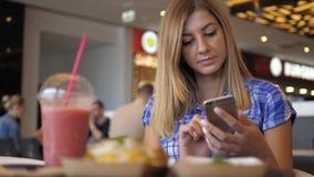 La mujer preciosa joven en camisa a cuadros azul se sienta en las aplicaciones Smartphone del café metrajes