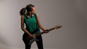 La mujer preciosa juega en la guitarra y escucha la música metrajes