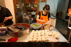La mujer prepara el bollo taiwanés hecho a mano de la carne en su parada imagen de archivo
