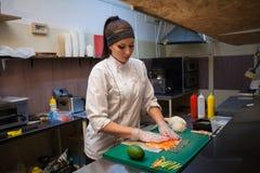 La mujer prepara el sushi fresco delicioso en la cocina en el restaurante imagen de archivo libre de regalías