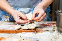 La mujer prepara las bolas de masa hervida, cocinando en casa, sano y sabroso foo imagenes de archivo