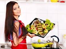 La mujer prepara pescados en horno. Fotografía de archivo