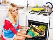 La mujer prepara pescados en horno. Foto de archivo libre de regalías