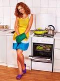 La mujer prepara pescados en horno. Fotos de archivo