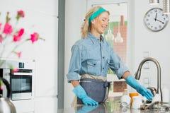 La mujer prepara platos para limpiar fotos de archivo