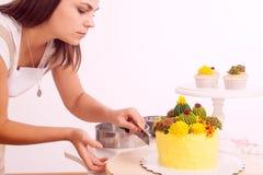 La mujer prepara la torta fotografía de archivo libre de regalías
