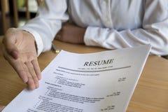 La mujer presenta la solicitud de trabajo, entrevistador que lee un curriculum vitae imagen de archivo libre de regalías