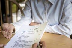 La mujer presenta la solicitud de trabajo, entrevistador que lee un curriculum vitae imagen de archivo