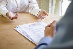 La mujer presenta la solicitud de trabajo, entrevistador que lee un curriculum vitae foto de archivo