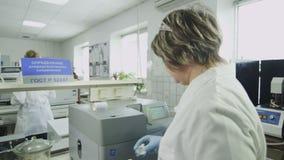 La mujer presiona los botones en el dispositivo de la prueba en laboratorio almacen de metraje de vídeo