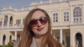 La mujer principal del jengibre feliz es sonrisa, colocándose al aire libre en día de primavera soleado almacen de metraje de vídeo