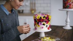 La mujer profesional del confitero adorna la torta con las flores en el estudio moderno blanco de la cocina El cocinero de sexo f almacen de metraje de vídeo