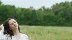 La mujer profundamente relajada en campo verde toca su pelo con los ojos cerró unicidad almacen de video