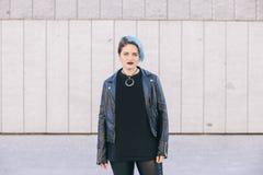 La mujer punky joven con el azul teñió el pelo y una chaqueta de cuero Fotos de archivo