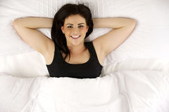 La mujer puso en considerar relajado de la cama para arriba la sonrisa de la cámara Fotos de archivo libres de regalías