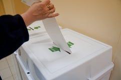 La mujer puso la balota de la elección en el rectángulo Imagen de archivo