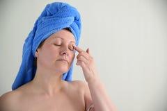 La mujer puso la crema en piel del párpado después de una ducha imágenes de archivo libres de regalías