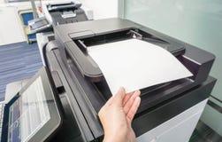 La mujer puso la hoja de papel en la impresora Fotos de archivo libres de regalías