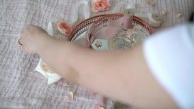 La mujer puso las flores en la bandeja rosada con el anillo y el perfume nupciales de la oferta de los pendientes almacen de video