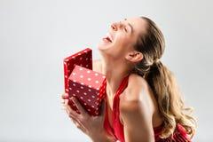 La mujer que abre el regalo y es feliz Fotografía de archivo libre de regalías
