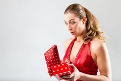 La mujer que abre el regalo y es feliz Fotos de archivo libres de regalías
