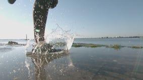 La mujer que activa que camina en el agua con salpica y cae almacen de video