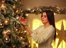 La mujer que adorna el ` s del Año Nuevo del árbol de navidad juega en casa Imagenes de archivo