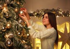 La mujer que adorna el ` s del Año Nuevo del árbol de navidad juega en casa Foto de archivo libre de regalías
