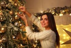 La mujer que adorna el ` s del Año Nuevo del árbol de navidad juega en casa Fotografía de archivo