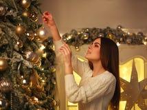 La mujer que adorna el ` s del Año Nuevo del árbol de navidad juega en casa el preparat Fotografía de archivo libre de regalías