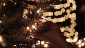 La mujer que adorna las luces en un árbol de navidad con el bokeh enciende el fondo almacen de metraje de vídeo