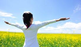 La mujer que anima abre los brazos en el campo de flor del col Fotos de archivo