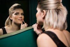 La mujer que aplica los labios glosa mientras que mira el espejo Fotos de archivo libres de regalías