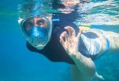 La mujer que bucea en agua azul muestra muy bien por los fingeres El bucear en mascarilla completa Foto de archivo libre de regalías