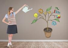 La mujer que celebra la regadera y el dibujo de los gráficos de negocio en la planta ramifica en la pared Imagen de archivo libre de regalías