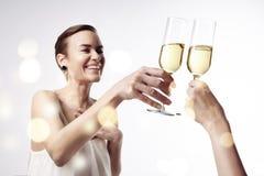 La mujer que celebra y dice alegrías en el partido con un vidrio de champán Vidrios del sonido metálico junto Imágenes de archivo libres de regalías